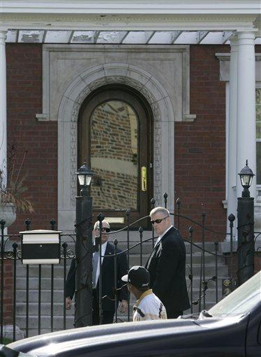 Dua anggota keamanan sedang melihat pejalan kaki di depan rumah Obama